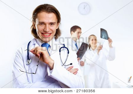 Young confident and friendly doctor in medical office