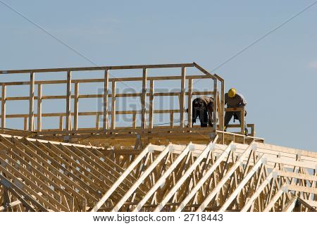 Workmen On Top Of Building