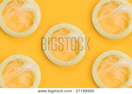 Set of yellow condoms on orange background
