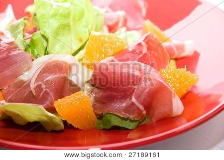 Close up of gammon salad at red dish on white