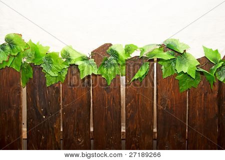 Part of wooden fence on white wall background