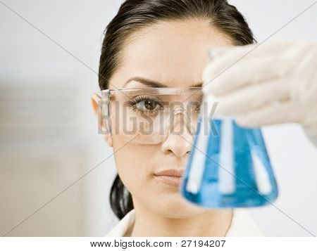 Female scientist looking at beaker of liquid