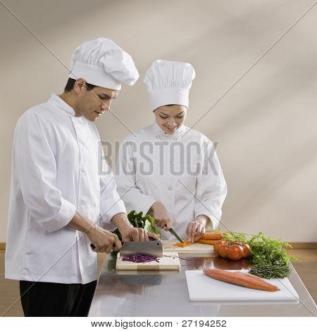 männlichen und weiblichen Chef Gemüse Hacken