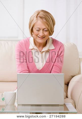 Senior woman typing on laptop on sofa at home