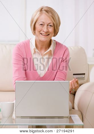 Happy senior woman making online shopping purchase on laptop with credit card