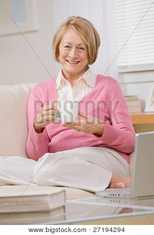 Content senior woman relaxing with tea on sofa at home