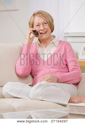 Happy senior woman talking on cell phone on sofa at home