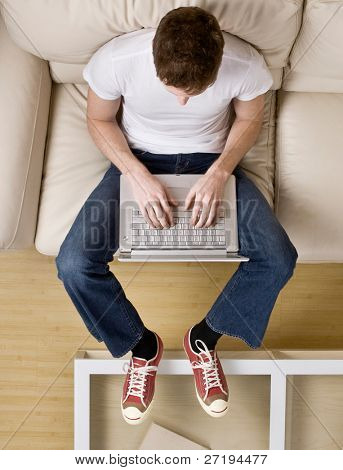 High angle view of cool young man typing on laptop on sofa at home