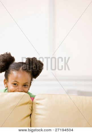 Cute, mischievous African girl hiding behind sofa