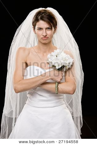 Studio shot of frowning young bride in wedding dress and veil