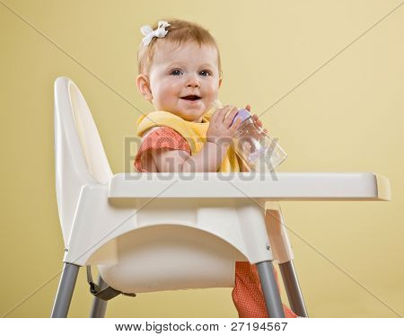 Happy baby girl sitting in highchair holding bottle