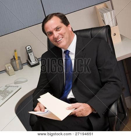 Happy businessman holding file folder at desk in cubicle