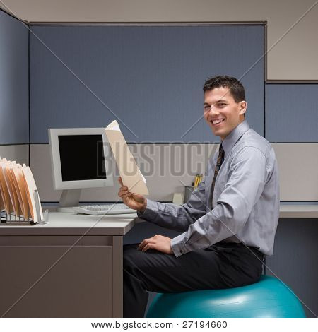 Smiling businessman sitting on exercise ball at desk in cubicle