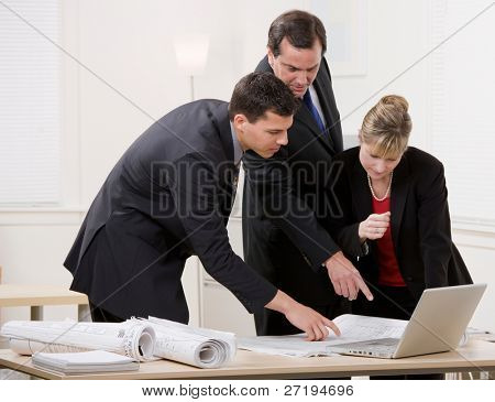 Architect co-workers collaborating on blueprints
