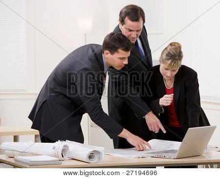 Compañeros de trabajo colaborando en planos de arquitecto