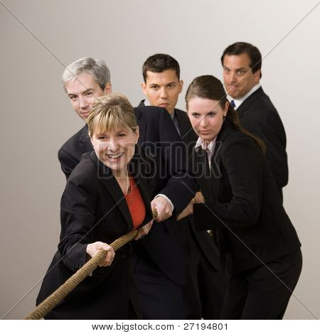 Group of determined co-workers pulling rope in tug-of-war