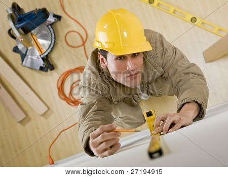 Construction worker in hard-hat using measuring tape for project