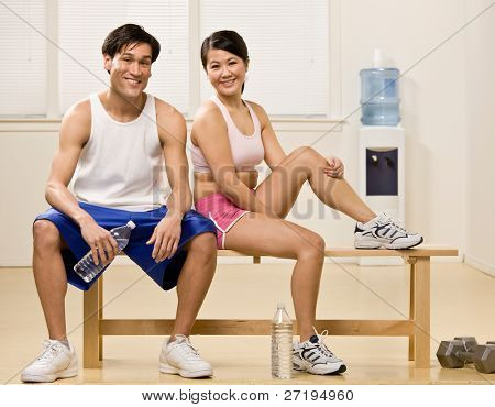 Fatigued man and woman holding water bottles in health club