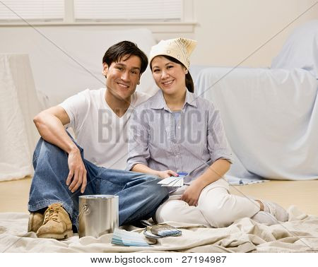 Couple sitting with paint can and paint swatch preparing to decorate home interior