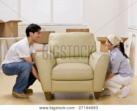 Couple moving into new home and placing armchair in livingroom