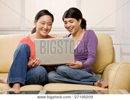 Barefoot friends enjoying using the laptop on sofa in livingroom