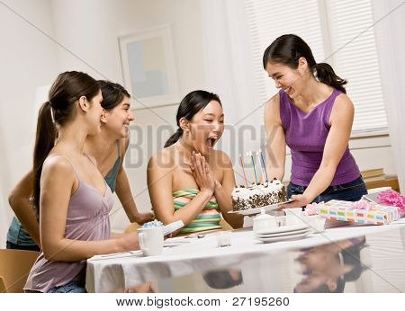Generous woman surprising friend with birthday cake at party