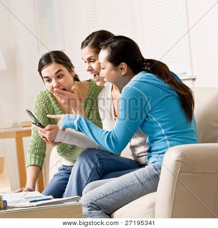 Shocked friends pointing and reading surprising text message on cell phone