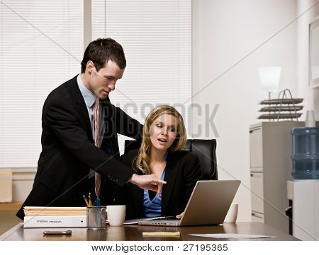 Co-worker listening to supervisor explain work on laptop