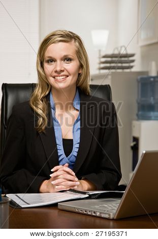 Happy, confident businesswoman reading report at desk