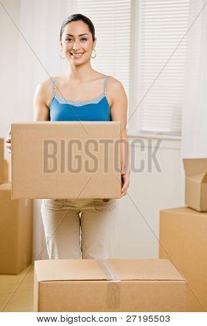 Mujer feliz mudarse a casa nuevo y llevar la caja de cartón