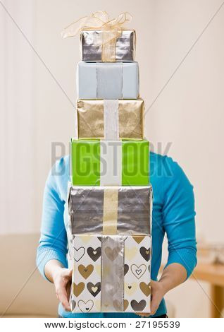 Generous woman carrying stack of festive birthday gifts