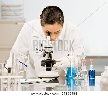 Curious research scientist in lab coat and rubber gloves looking at specimen under microscope in laboratory