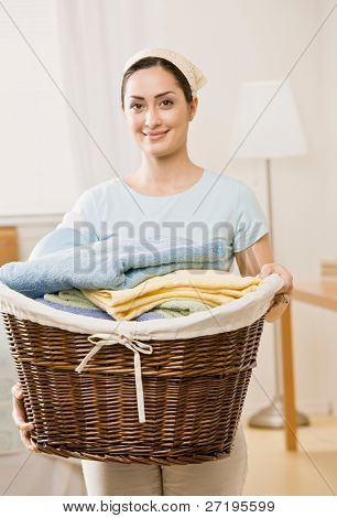 Housewife holding full basket of laundry