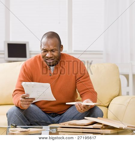 Confused man constructing wooden shelf and reading instructions