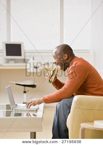 Hungry man multi-tasking by eating a sandwich and typing on laptop in livingroom