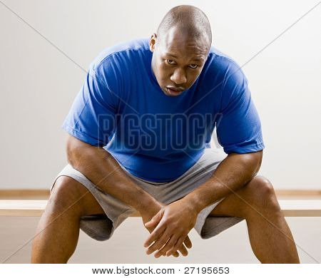 Fatigued man leaning on knees in health club