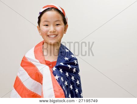Patriotic girl with American flag around her shoulders and American flag headband