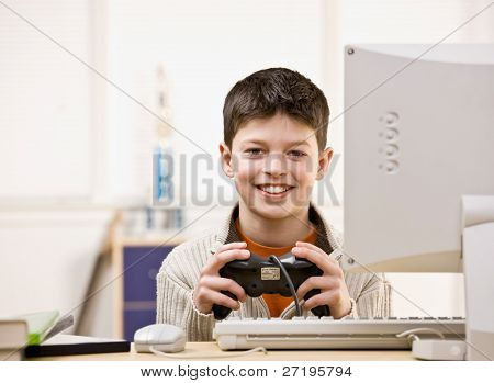 Boy holding video game controller having fun playing video game on computer