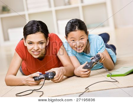 Determined friends having fun using video game controllers to play exciting video game