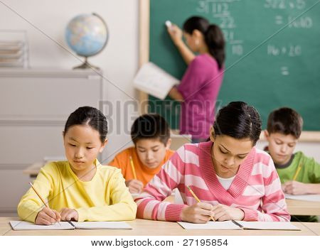 Concentrating students writing in notebook in school classroom