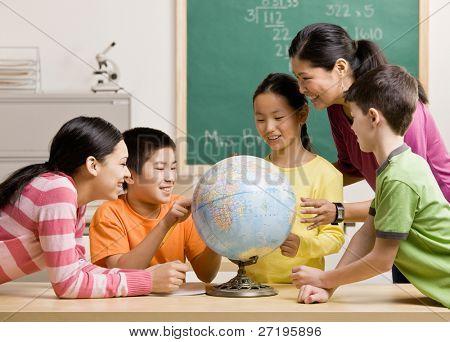 Profesor y los alumnos viendo el globo en el aula de geografía