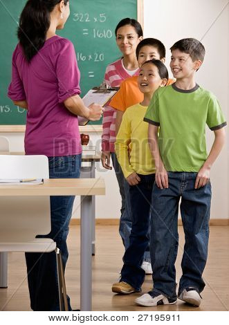 Students listen to teacher with clipboard in school classroom
