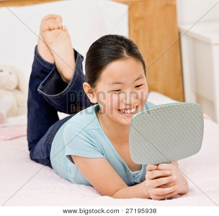 fröhlich, zuversichtlich Mädchen mit auf Bett anzeigen Reflektion im Spiegel