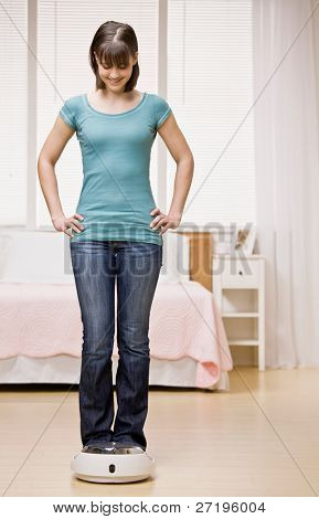 Confident teenager checking success of diet by weighing herself on scale