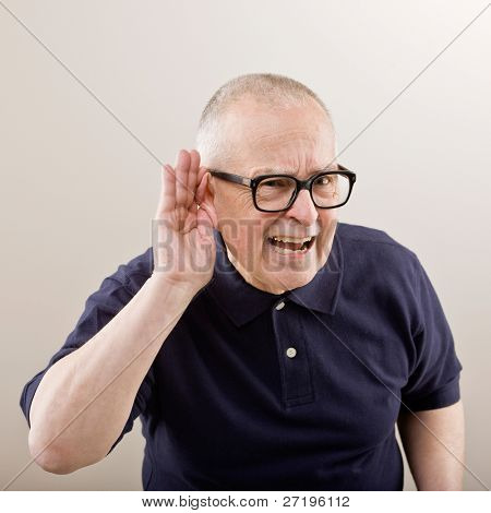 Man cupping his ear having difficulty hearing