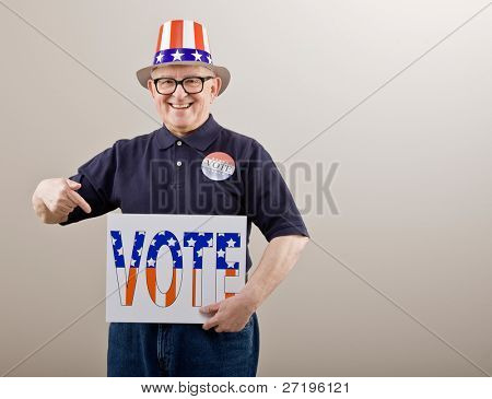Patriotic man in American flag hat and vote button pointing to vote sign
