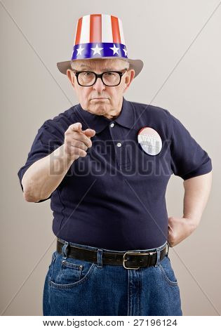 Frowning patriotic man in American flag hat and vote button pointing accusingly