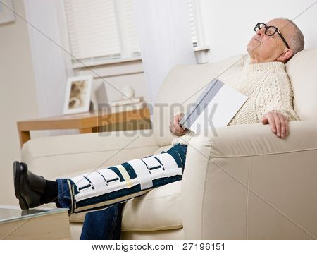 Disabled man with leg brace holding book and napping on sofa in livingroom