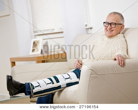Disabled man with leg brace sitting on sofa in livingroom