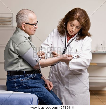 Sick patient having blood pressure taken by doctor during checkup